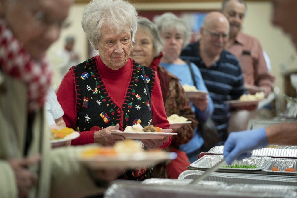 "Donna Ames, 83, of Portland waits in the serving line at a Christmas day meal at Westbrook-Warren Congregational Church in Westbrook on Tuesday. ""It's just great,"" she said. ""They do a great job and the people here are just wonderful."" She was dining before her night shift at Spring Harbor Hospital."