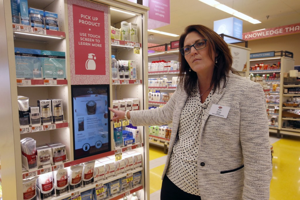 Kim Gray, director of Hannaford's center store merchandising, demonstrates a touchscreen that automatically activates whenever a product is selected by customers and offers additional information. The store has rolled out new tech as part of a reorganization within the Forest Avenue store.