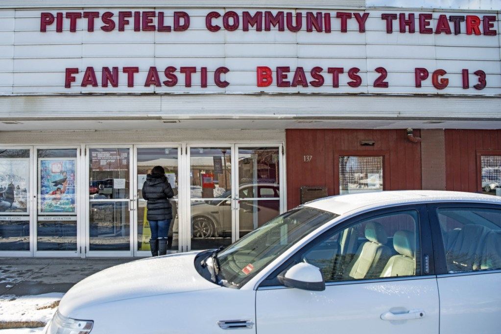 """Theresa Butler looks at showtimes Thursday at the Pittsfield Community Theater on Main Street in Pittsfield. Butler said the theater is the """"only thing they have going in town that parents bring their children to."""""""