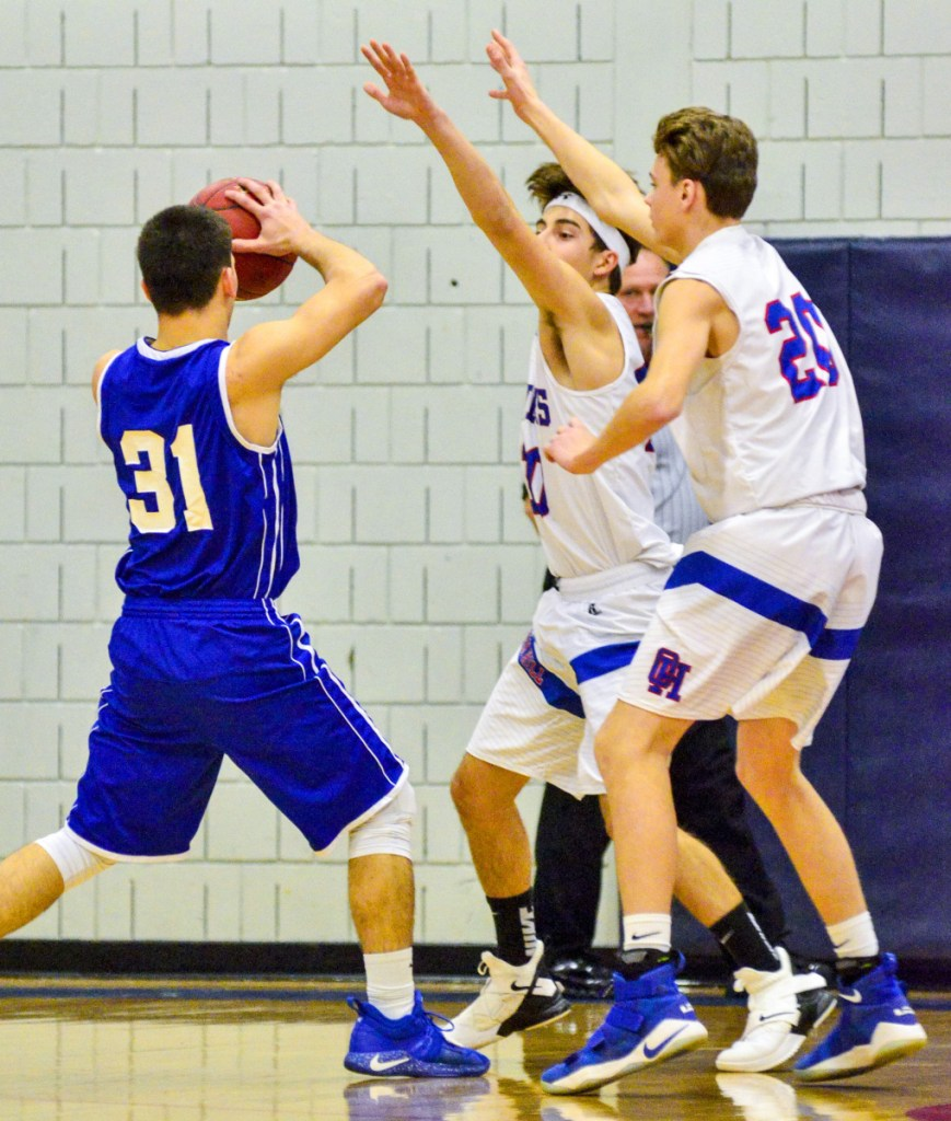 Madison's Eric Wescott, left, is defended by Oak Hill's  Gabe Samson and Isiah Morgan (25) during a Mountain Valley Conference game Thursday in Wales.