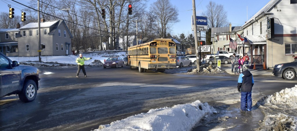 A crossing guard halts traffic for RSU 18 school children at the intersection of Oak and Pleasant streets in Oakland on Tuesday. The spot is busy with traffic and is in the middle of four school buildings.