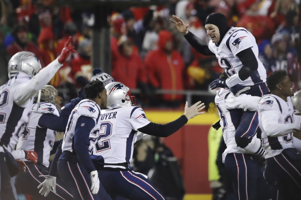 New England Patriots quarterback Tom Brady (12) celebrates with his teammates after they won the AFC  championship Sunday in Kansas City.