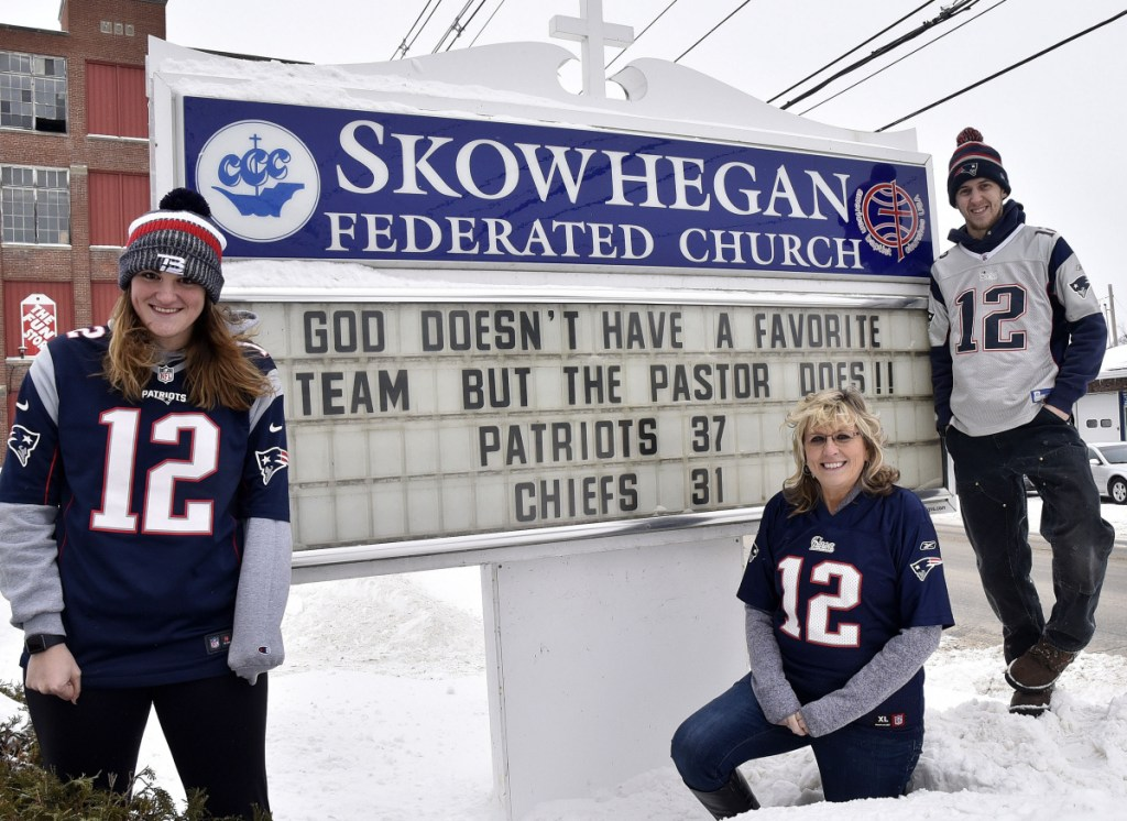 Members of the Mark and Deb Tanner family, hardcore fans of the New England Patriots, gather around a sign at the Federated Church in Skowhegan on Monday. Deb Tanner, center, is flanked by children Kaley and Josh. Her husband, the Rev. Mark Tanner, is out of state this week but picked the correct score of the AFC championship game against the Kansas City Chiefs.