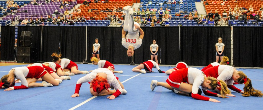 Kennebec Journal photo by Joe Phelan   Cony's Ethan Overlook does a flip at the end of the Rams' performance during the Class A North regional cheering competition Saturday at the Augusta Civic Center.