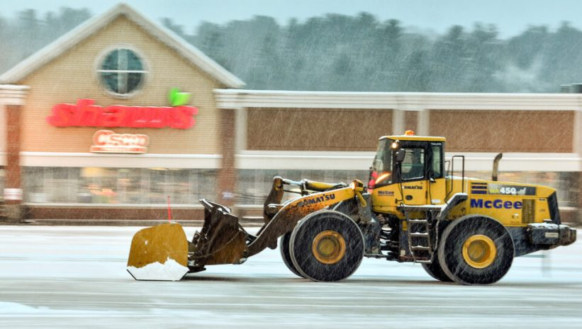 A front-end loader clears the parking lot around 7:15 a.m. Wednesday at Shaw's Plaza in Augusta.