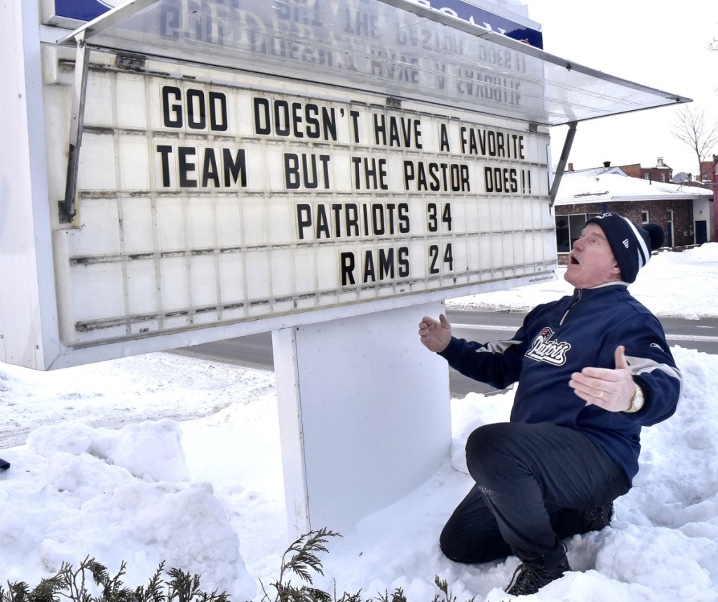New England Patriots fan the Rev. Mark Tanner makes his Super Bowl prediction known publicly Thursday outside the Federated Church in Skowhegan by posting a notice that the Patriots will beat the L.A. Rams, 34-24.