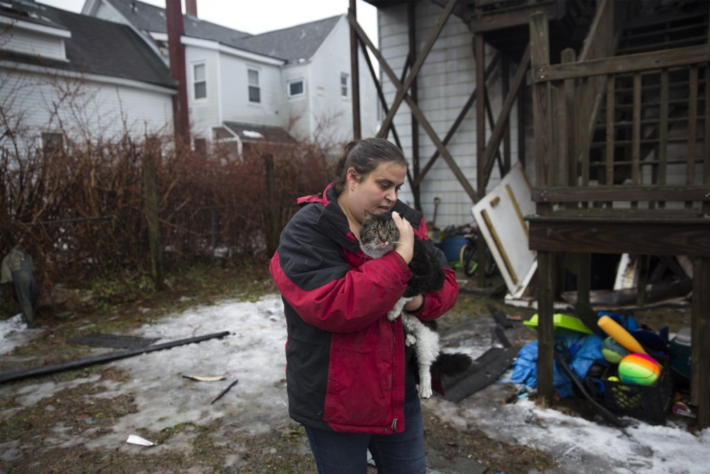 "Jolean Beane carries her sister-in-law's cat Jax back to her car after she caught him outside of the apartment building that caught fire on Swett Street in the early morning on Wednesday, January 9, 2019. Bean said her sister-in-law's family escaped the fire and left the backdoor open as they left. They didn't know what happened to their cat Jax. Beane spent the morning looking for him and finally found him as he ran back to his home. ""We didn't think there was any way the cat got out,"" Beane said. ""The kids will be so happy."""