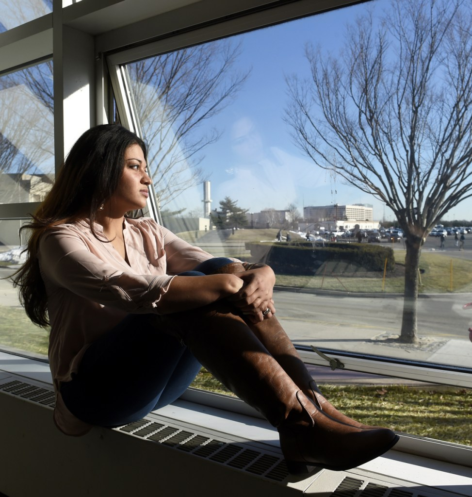 """Naila Amin, 26, looks out from a window at Nassau Community College in Garden City, N.Y. """"My passport ruined my life,"""" said Amin, a dual citizen from Pakistan who was forcibly married at 13 and applied for papers for her 26-year-old husband to come to this country."""
