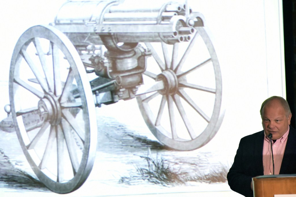 State Archivist Dave Cheever displays on Sunday an image of a Gatling gun while discussing the history of the Second Amendment during a forum at the University of Maine at Augusta. A Gatling gun was placed in the lobby of the State House, Cheever said, to try to deter mob violence about the gubernatorial election of 1879. The state supreme court eventually ruled in January 1880 that Gov. Daniel Davis has won the governorship.