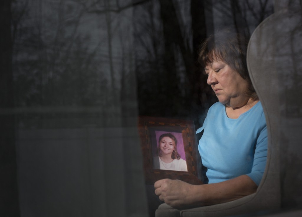 "Lise Ouellette of Old Orchard Beach holds a portrait of her daughter Ashley, who was killed 20 years ago in a case that remains unsolved. ""There's no time limit on grieving,"" says the anguished mother, who still hopes for resolution. ""I just want to know why."""