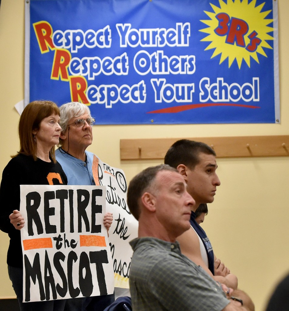 Lisa Savage, back left, and Mark Roman, back center, stand with signs calling for the Skowhegan Area High School Indian mascot be retired during an April 7, 2016, School Administrative District 54 board meeting at Skowhegan Area Middle School.