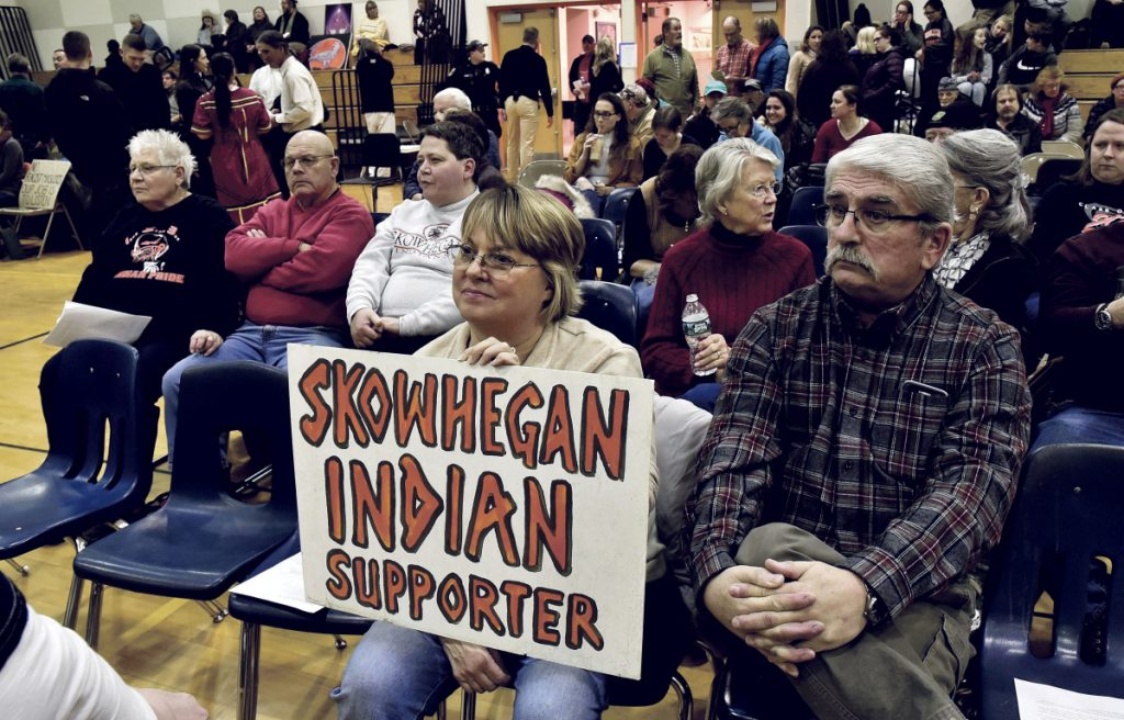 Gloria and Ken Gordon, of Skowhegan, hold a sign in favor of keeping the Indian mascot during a School Administrative District 54 school board meeting in January.