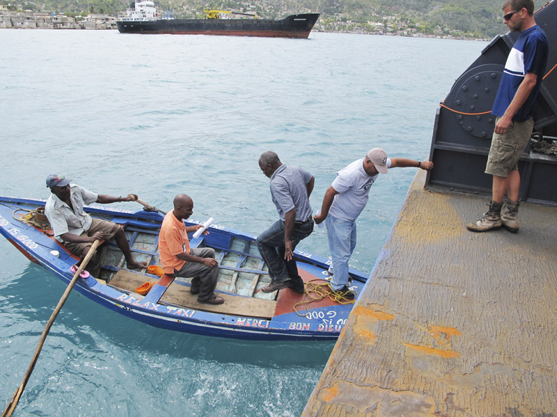 Sea Hunter volunteer Rick Woodbury of Scarborough, right, watches as Haitian officials depart the ship Friday morning. The deep-water dock in Miragoane is in sight, but is stillunattainable.