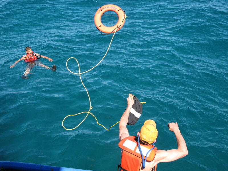 Sea Hunter deckhand Alex Bezkorovainy throws a life ring to volunteer Rick Woodbury of Scarborough during a safety drill on Saturday off Miami.