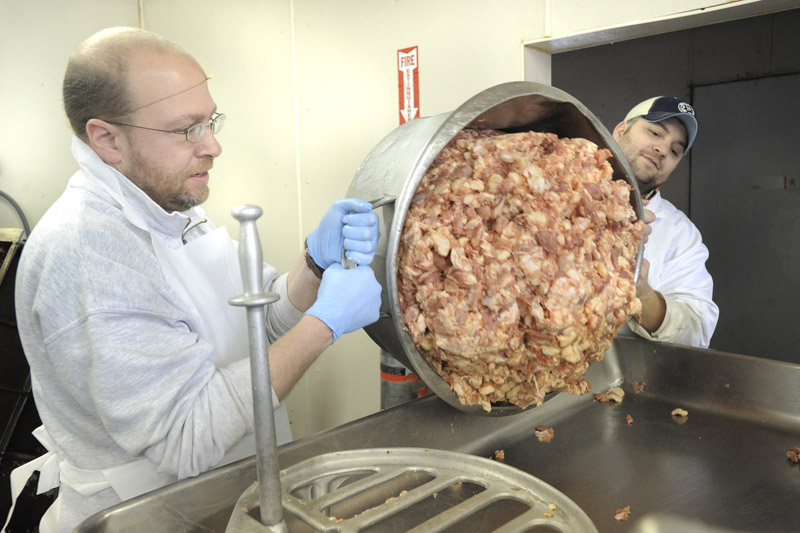 Reporter Ray Routhier, left, helps Marc Mailhot pour a container of pork into the grinding machine while learning the sausage business at Mailhot's Best, in Lewiston.