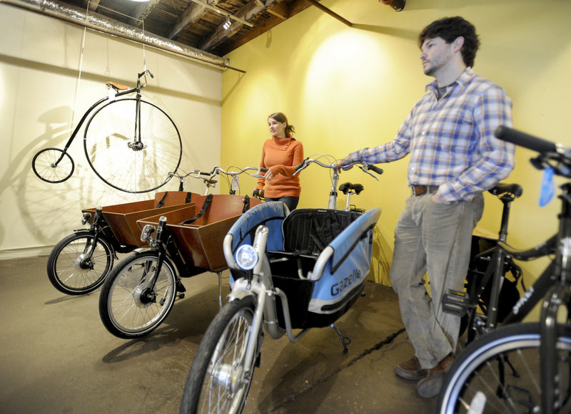 Gillian Kitchings and Josh Cridler own and operate Portland Velocipede, a bicycle shop recently opened in Portland. The new owners are seen with Dutch box bikes, that allow riders to carry lots of items, like groceries, and also give a comfortable ride.