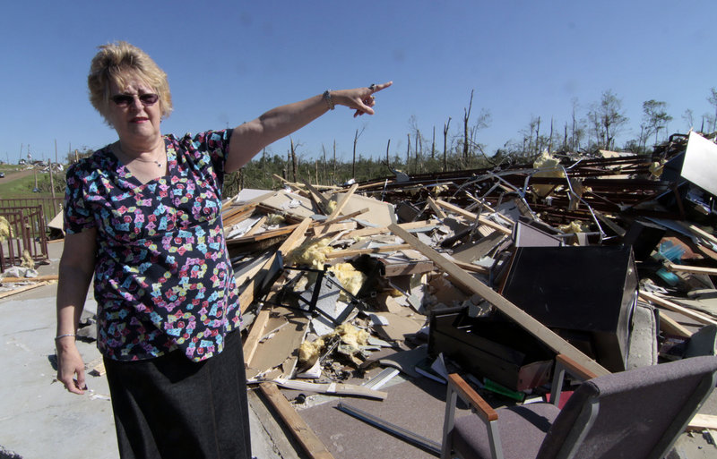 Hillcrest Baptist Church member Carolyn Porter stands amid the rubble of the Yazoo City, Miss., structure on Sunday. Porter and other members held a brief morning service before searching through the debris for Bibles, hymnals and other church-related materials. The church was destroyed by one of several tornados that blew through the state on Saturday.