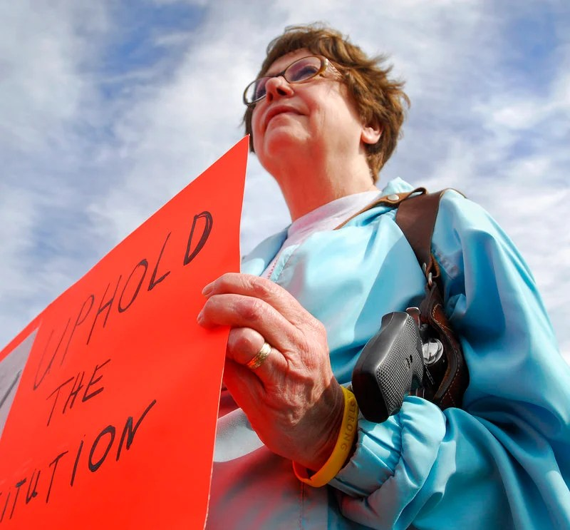 """Mary Lou Bagley, 63, of Portland carries a .38-caliber Smith & Wesson and holds a sign reading """"Uphold the Constitution"""" at Back Cove in Portland during an open-carry gathering Sunday."""