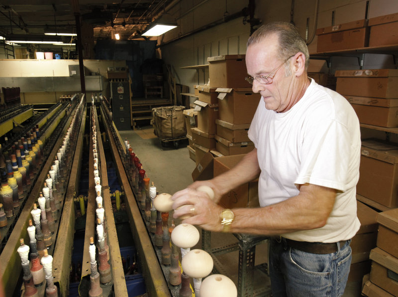 Neil Evans puts pepper-grinder tops on spindles that will run them through a painting machine at the Vic Firth factory.