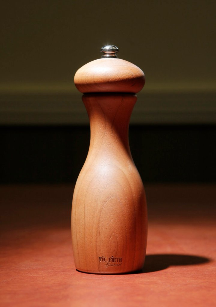 A pepper grinder made of cherry wood.