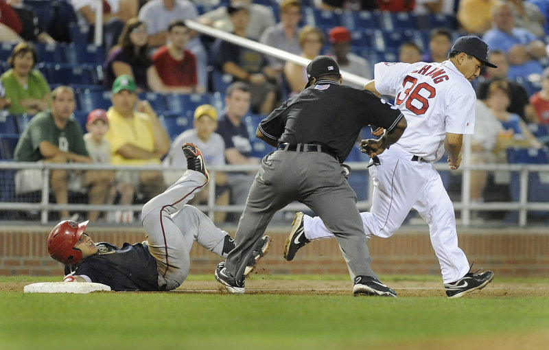 Umpire Doug Vines calls out Harrisburg's Jhonatan Solano after a tag by Portland third baseman Ray Chang on Monday night at Hadlock Field. Solano tried to take third base after his RBI double in the sixth inning.