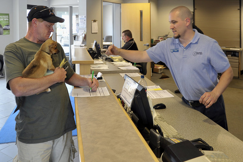Jim Dugan, left, of Waterford signs for service on his car at Goodwin Chevrolet Buick Pontiac in Oxford, as Service Manager Thom Bell assists last week. The service department provided a significant part of the firm's income while the dealership awaited word from General Motors about its fate, Goodwin officials said. The Service Center soon will be open Saturdays.