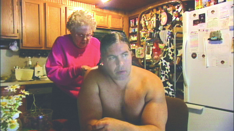 """Stan Pleskun's mother braids his hair in """"Strongman."""" The movie follows Pleskun's efforts to make a reputation with his physical gifts."""