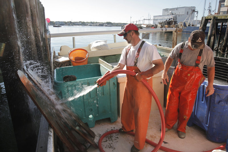 Rob Boynton, left, hoses down pen boards while he and Jay Roberts clean up Thursday after two days of fishing for pollock, hake and cod.