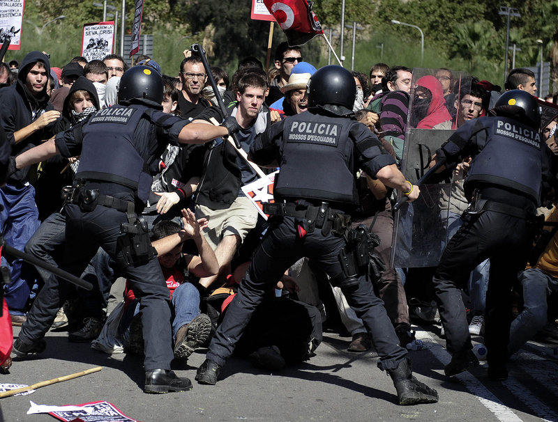 Riot police push back a wave of demonstrators during protests Wednesday in Barcelona, Spain. Spanish workers staged a general strike Wednesday to protest austerity measures imposed by a government struggling to slash its budget deficit and overcome recession.