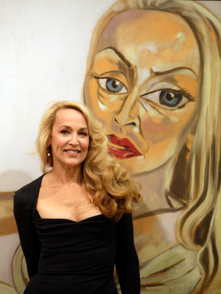 """Model and actress Jerry Hall poses with Francesco Clemente's 1997 oil on canvas titled """"Jerry Hall,"""" one of the artworks auctioned Saturday."""