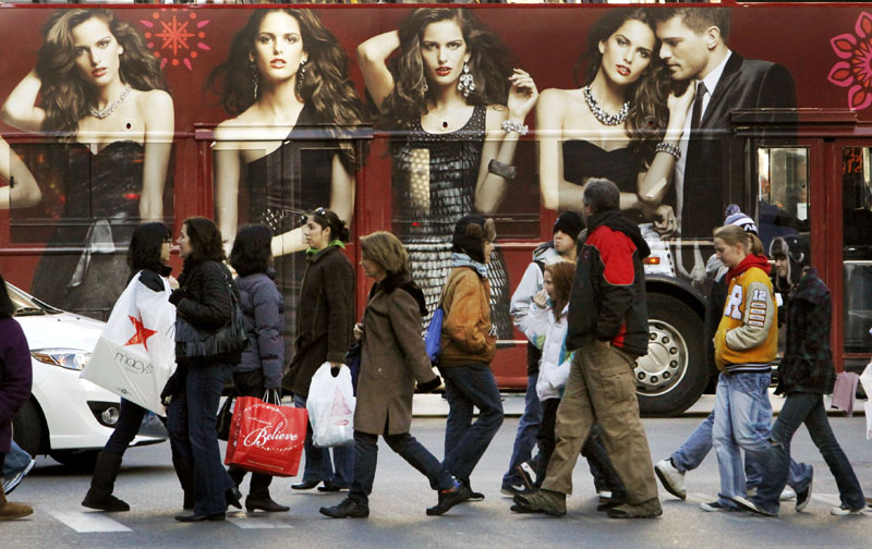 Shoppers walk in front of a tour bus with an Express clothing store ad on the side recently in Chicago.