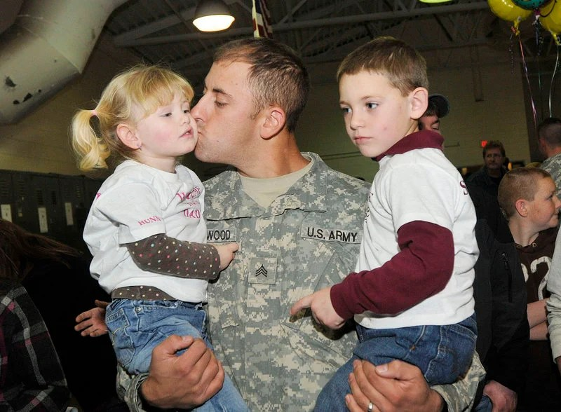 Sgt. Alan Stanwood of Harrington gives his daughter Natalie, 2, a kiss as he holds his son Michael, 5, after returning with the Maine Army National Guard's Bravo Company, 3rd Battalion, 172nd Mountain Infantry in Bangor on Thursday.
