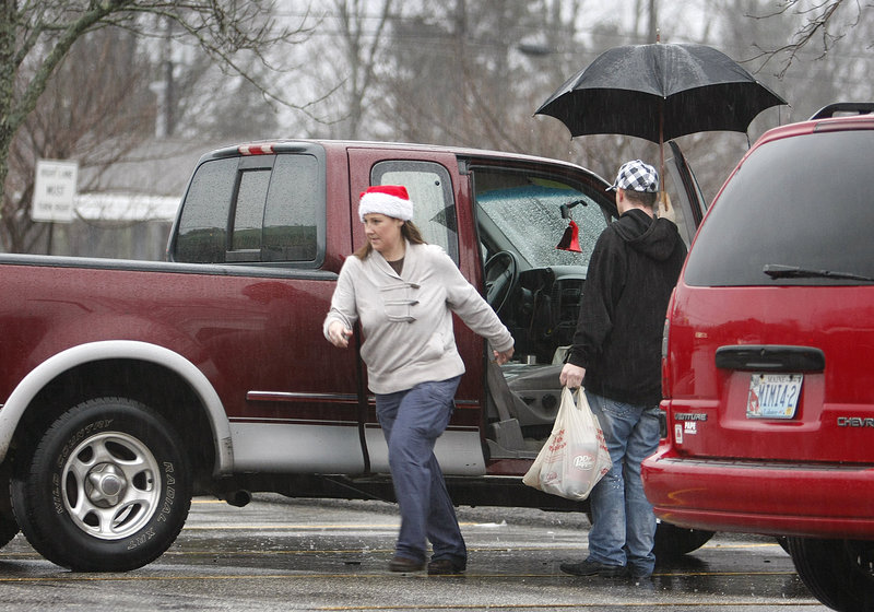 Michelle Minor dashes for cover after loading groceries with Derek Cote at Hannaford in Saco on Sunday. The two live in Old Orchard Beach. The rain is expected to continue today, but winds should die down.