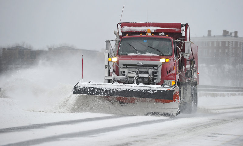 A snowplow cleans the road crossing Martin's Point Bridge between Portland and Falmouth. Public works crews in several municipalities spread sand and salt on the streets even before the first flake fell to minimize slippery conditions.