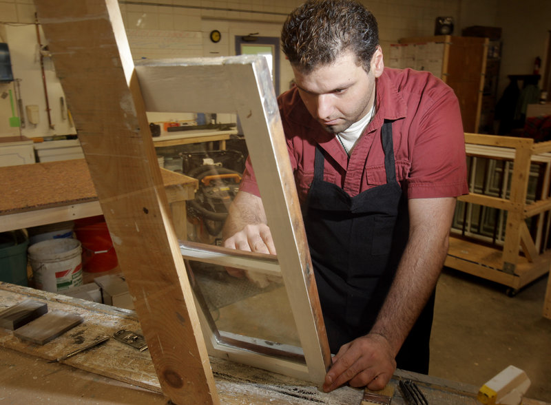Navid Ahadzadeh cleans a window at Bagala Window Works in Falmouth. Owner Marc Bagala will conduct a series of window restoration workshops beginning in February. Below: Frames being restored at Bagala Window Works.
