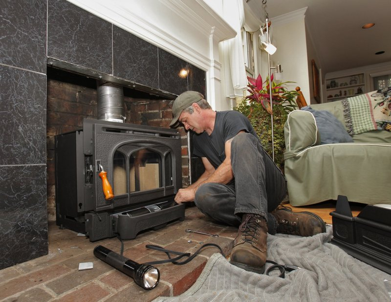 Craig McCausland installs a wood-burning fireplace insert at a Falmouth condo in the fall of 2009. A federal tax credit cut the cost of the improvement by 30 percent.