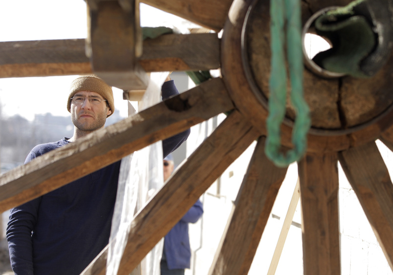 Boat builder Clint Chase holds a brace as a mast wheel is moved into his shop on Fox Street in Portland.
