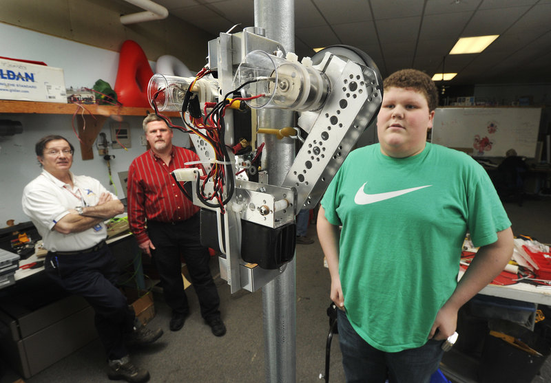 "Chris Fearing, a member of South Portland High School's robotics team, watches a ""mini-bot"" climb a 10-foot pole. Also watching the test, from left, are Steve Martin and Jim Henningsen, mentors to the group."