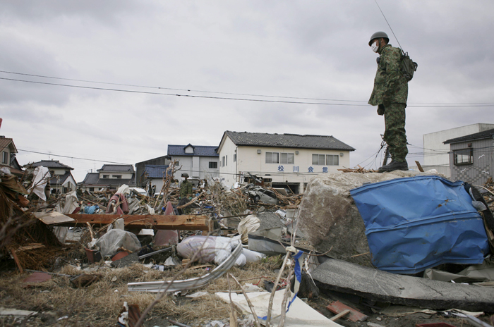 A member of Japan's Self-Defense Force surveys the damage in Soma, Fukushima prefecture.