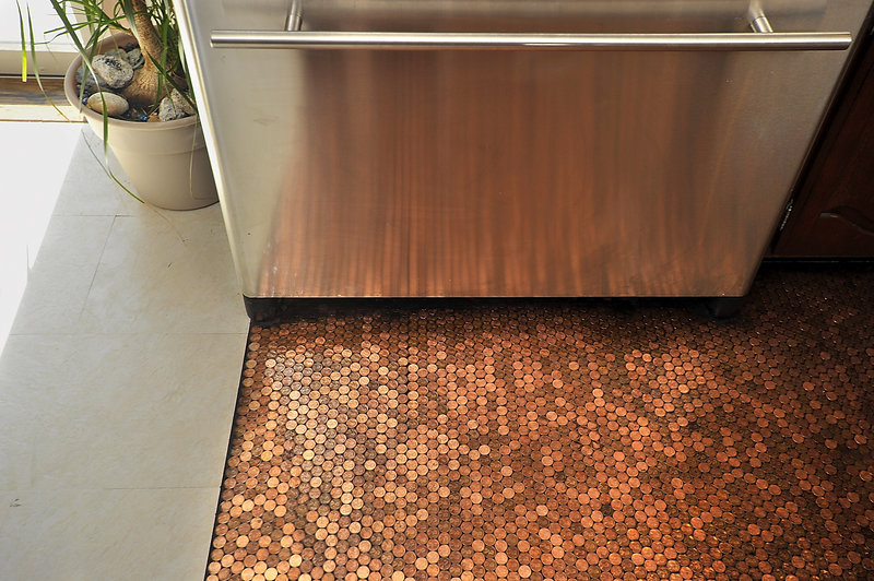 """Edwards' stainless-steel refrigerator reflects the rich coppery patina of the pennies she used to create her kitchen floor. """"When the sun hits it just right, this floor just glows,"""" says Edwards."""