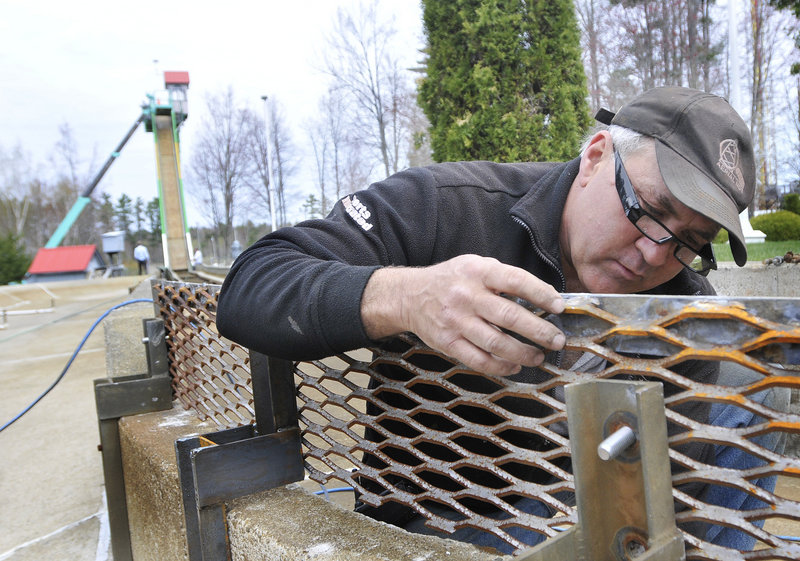 Billy Cormier replaces a bolt as part of the preventive maintenance for the Thunder Falls Log Flume at Funtown/ Splashtown USA.