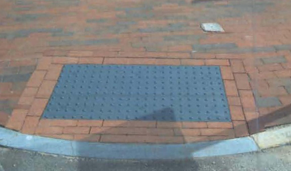 Curb cuts like the one at left textured gray tiles bordered by brick will be installed in Portland s historic districts as a cue to visually impaired people of areas where the sidewalk meets the street.