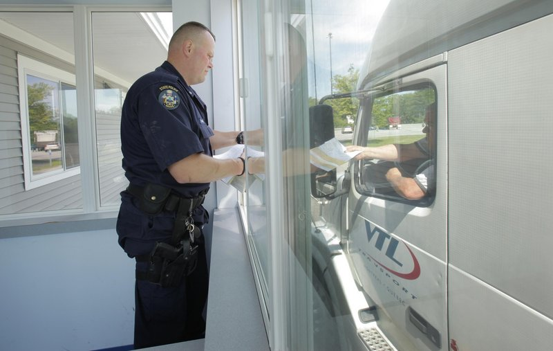 Maine State Police Trooper Shane Northup takes paperwork from a truck driver during a truck check at a weigh station off the northbound lane of the Maine Turnpike in York on Tuesday.