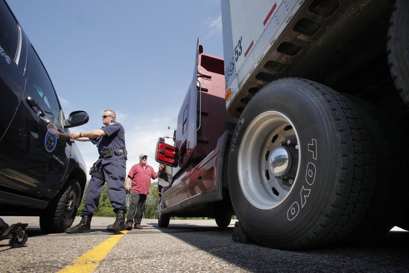 State Trooper Shane Northrup checks a truck driven by Tom Becker of Lagrange in York on Tuesday, the first day of a three-day annual truck enforcement effort. Becker was driving a load of groceries to Hannaford in South Portland.