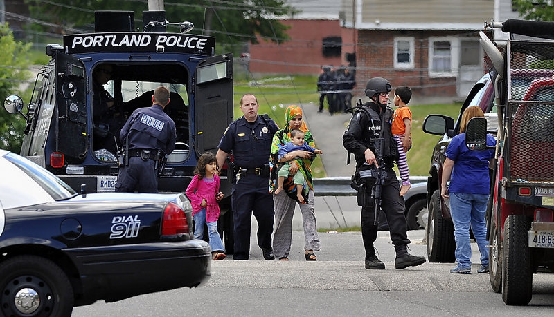 Nicholas Goodman, right, a member of the Special Reaction Team, carries a child after a standoff at the Riverton Apartments complex in Portland in 2011.