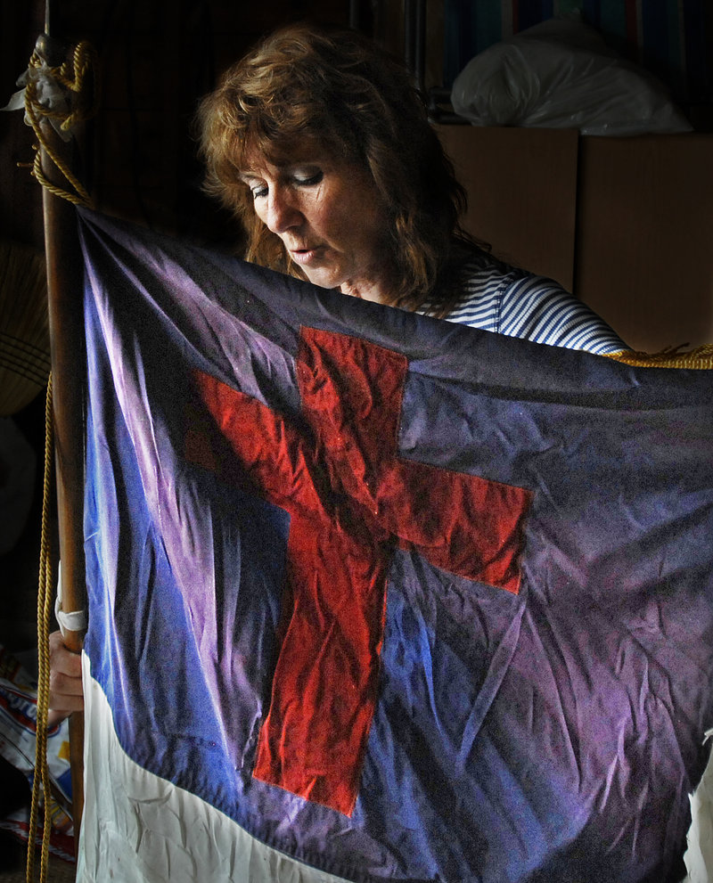 Deb Baker holds a Christian flag that she said had been hanging in the back of the Raymond Hill Baptist Church since she was a child. Baker, who lives less than a half-mile away, retrieved the flag Tuesday night after a fire severely damaged the building.