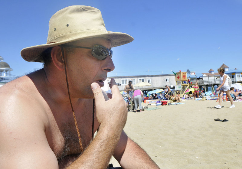 Visiting from Canada, Ali Guvenc smokes in Old Orchard Beach on Thursday. Responding to a proposed ban on smoking on the town's public beaches, he questioned how the government can justify further restricting an activity that is legal for those 18 and older.