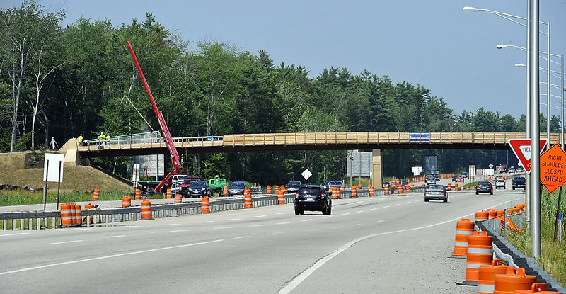 A rail is lowered into place as work on the Eastern Trail bridge over I-95 continues.