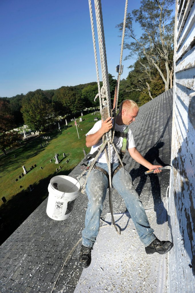 Nick Gustafson of MMR Professional Steeplejacks scrapes old paint from the steeple of the Old Meeting House in Yarmouth on Wednesday. The $30,000 restoration project was funded by the Town Council in June.
