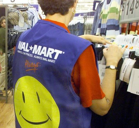 A customer service employee sorts through a clothing rack as patrons shop at the Walmart in North Richland Hills, Texas. . Starting next year, future part-timers will no longer qualify for insurance, and existing full-time employees will pay more of the cost.